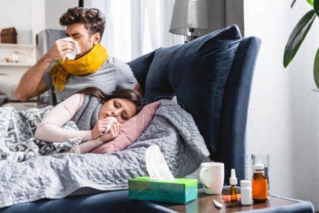 Photo pour Malade copine et beau petit ami éternuer et tenant des serviettes - image libre de droit