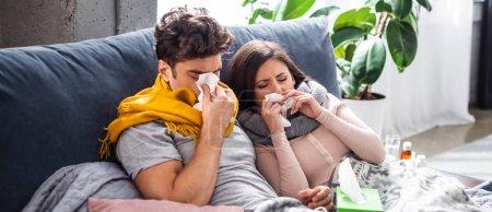 Photo pour Plan panoramique de petite amie malade et petit ami éternuant et tenant des serviettes - image libre de droit