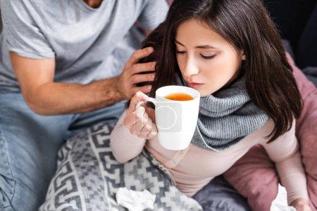 Photo pour Foyer sélectif de femme attrayante et malade boire du thé - image libre de droit