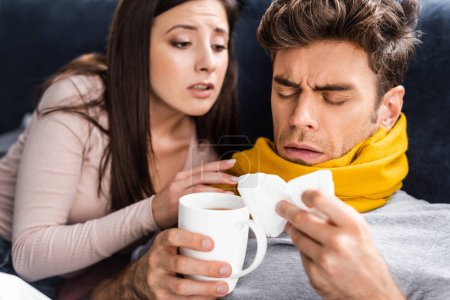 girlfriend looking at sick boyfriend with cup of tea and napkin