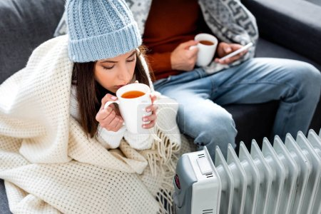 selective focus of attractive girlfriend with cup of tea warming up near heater