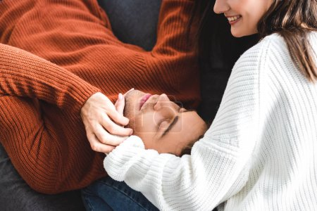 boyfriend lying on knees of girlfriend in sweater and smiling in apartment