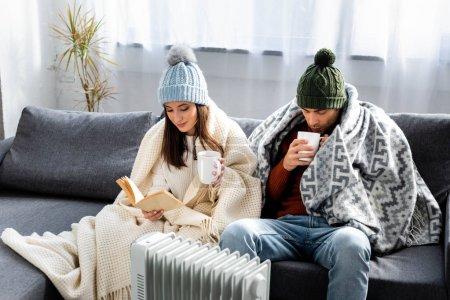 Photo pour Attrayant petite amie lecture livre et petit ami en tenue d'hiver avec tasse échauffement près de chauffage - image libre de droit