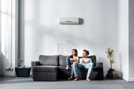 Photo for Attractive girlfriend and handsome boyfriend sitting on sofa in apartment - Royalty Free Image