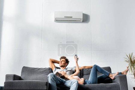 Photo pour Jolie copine allumant un climatiseur et allongée sur les jambes d'un beau copain - image libre de droit