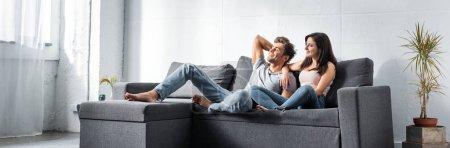 Photo pour Plan panoramique de jolie petite amie et beau petit ami assis sur le canapé - image libre de droit