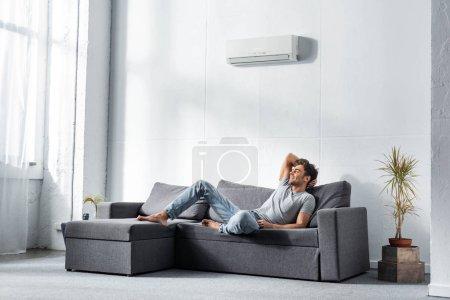 Photo pour Bel homme souriant en jeans et t-shirt couché sur le canapé - image libre de droit