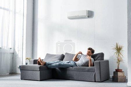 Photo pour Bel homme en jeans regardant un t-shirt et allongé sur un canapé - image libre de droit