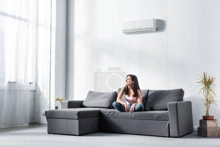 Foto de Una mujer atractiva y sonriente sentada en el sofá y mirando hacia otro lado - Imagen libre de derechos