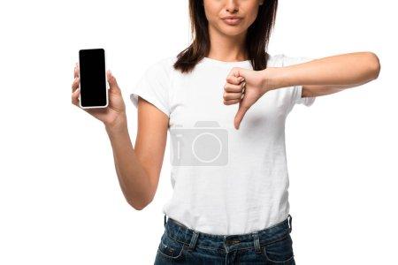 Ausgeschnittene Ansicht einer Frau, die Daumen nach unten zeigt und Smartphone mit leerem Bildschirm, isoliert auf weiß