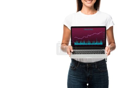 beautiful smiling woman showing laptop with trading app, isolated on white