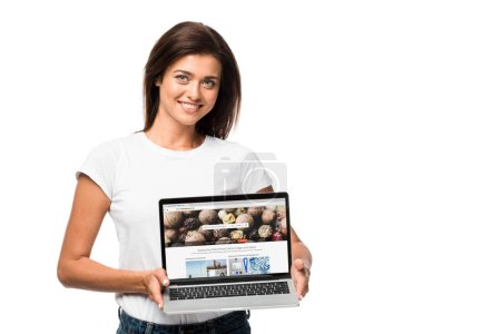 Photo pour KYIV, UKRAINE - SEPTEMBER 10, 2019: beautiful smiling woman showing laptop with depositphotos website, isolated on white - image libre de droit