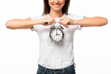 cropped view of smiling woman holding alarm clock, isolated on white