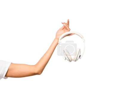 cropped view of young woman holding headphones, isolated on white