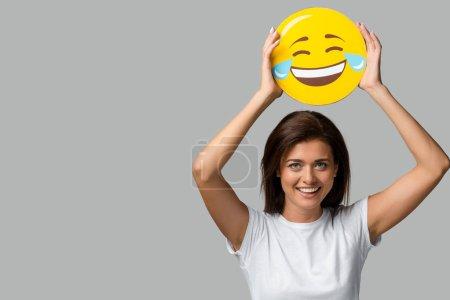 KYIV, UKRAINE - SEPTEMBER 10, 2019: beautiful smiling woman holding yellow laughing emoji, isolated on grey