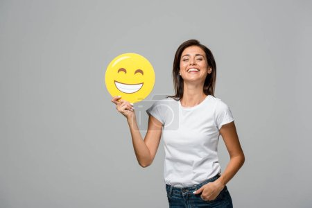 Photo for KYIV, UKRAINE - SEPTEMBER 10, 2019: cheerful woman holding yellow happy smiling emoji, isolated on grey - Royalty Free Image