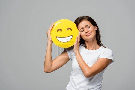 Photo pour KYIV, UKRAINE - 10 SEPTEMBRE 2019 : émotionnelle fille tenant jaune heureux sourire emoji, isolé sur gris - image libre de droit