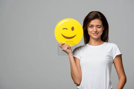 Photo for KYIV, UKRAINE - SEPTEMBER 10, 2019: beautiful smiling woman holding yellow winking emoji, isolated on grey - Royalty Free Image
