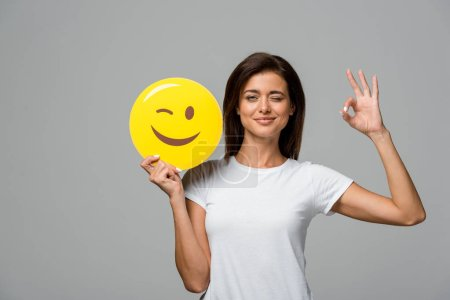 KYIV, UKRAINE - SEPTEMBER 10, 2019: beautiful woman holding yellow winking emoji and showing ok sign, isolated on grey