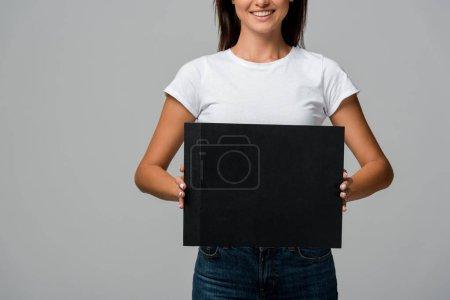 Photo pour Vue recadrée d'une femme souriante tenant une carte vide, isolée sur fond gris - image libre de droit