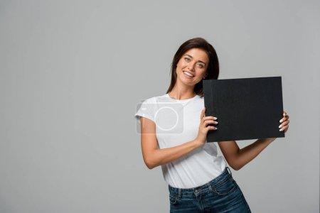 Photo pour Belle femme heureuse tenant tableau noir vide, isolé sur gris - image libre de droit