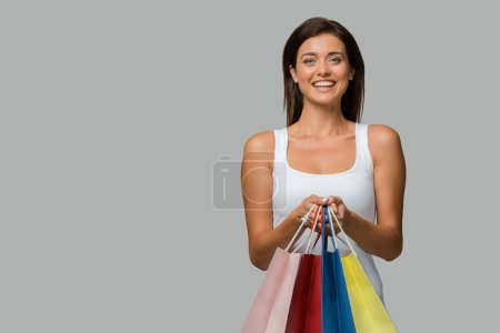 Photo for Beautiful smiling woman holding shopping bags, isolated on grey - Royalty Free Image