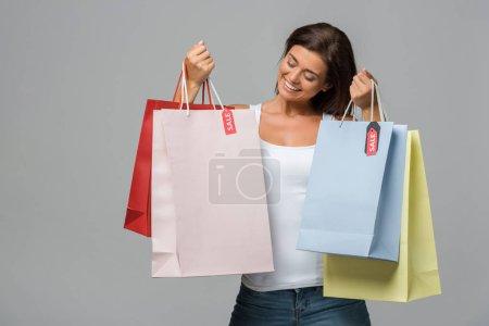 Photo pour Heureuse femme tenant des sacs avec des enseignes de vente, isolée sur grise - image libre de droit