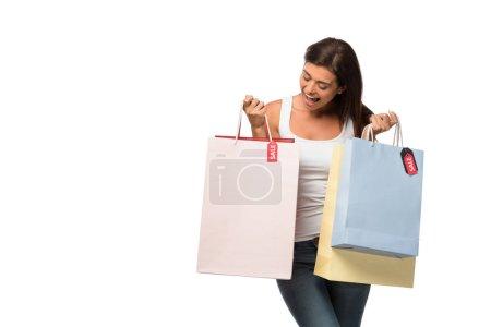 Photo pour Fille joyeuse tenant des sacs à provisions avec des enseignes de vente, isolée sur blanc - image libre de droit
