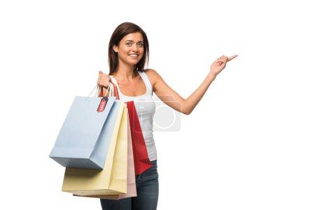 Photo pour Fille souriante tenant des sacs à provisions avec des signes de vente tout en pointant isolé sur blanc - image libre de droit