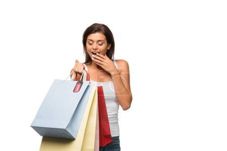Photo pour Fille surprise tenant des sacs à provisions avec des signes de vente, isolé sur blanc - image libre de droit