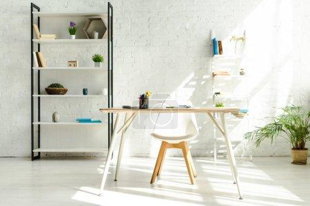 Foto de Interior de una oficina moderna con estanterías, mesa y silla. - Imagen libre de derechos