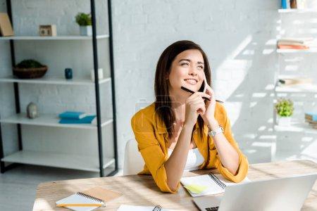 Photo pour Belle freelance rêveuse parler sur smartphone et travailler sur ordinateur portable au bureau à la maison - image libre de droit