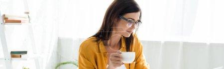 Photo pour Belle pigiste féminine dans les lunettes tenant tasse de café dans le bureau à la maison - image libre de droit