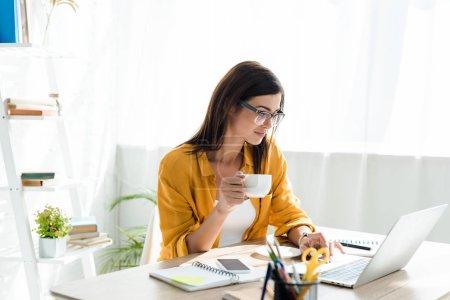 Photo pour Belle pigiste travaillant sur ordinateur portable avec tasse de café dans le bureau à la maison - image libre de droit