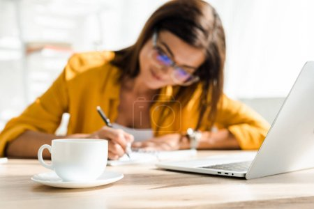 Photo for Selective focus of coffee cup and beautiful freelancer writing in home office - Royalty Free Image