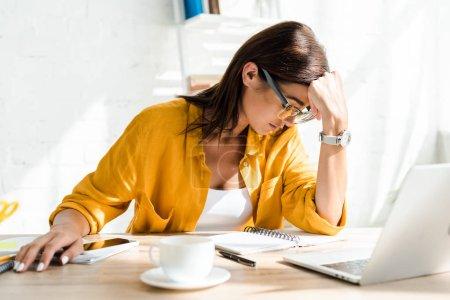 Photo pour Freelance fatigué travaillant sur ordinateur portable avec tasse de café dans le bureau à la maison - image libre de droit