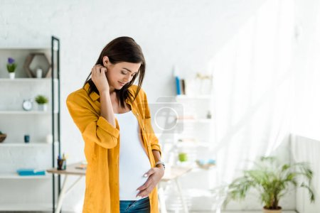 Photo for Attractive pregnant freelancer in yellow shirt touching tummy in home office - Royalty Free Image