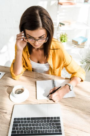 Photo pour Beautiful confident freelancer with coffee cup working with laptop and notebook in home office - image libre de droit