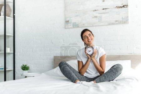 Photo pour Belle femme souriante assise au réveil sur le lit le matin - image libre de droit