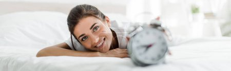 Photo for Selective focus of happy girl lying with alarm clock on bed in the morning - Royalty Free Image