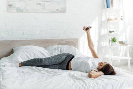 attraktives Mädchen macht Selfie auf dem Smartphone im Bett