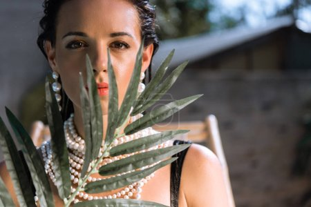 attractive woman in earrings with plant looking at camera