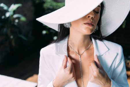 Photo for Attractive woman in white suit and hat posing with closed eyes outside - Royalty Free Image