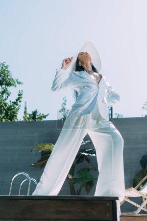 Photo pour Vue à angle bas d'une femme attrayante en costume et chapeau blancs posant à l'extérieur - image libre de droit
