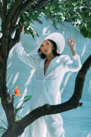attractive woman in white suit and hat posing and looking away outside