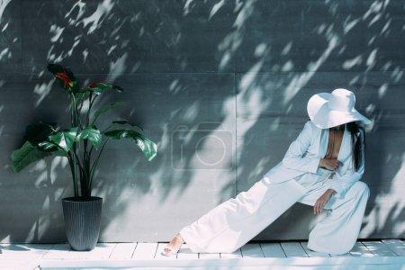 Photo pour Femme adulte en costume blanc et chapeau posant à l'extérieur - image libre de droit