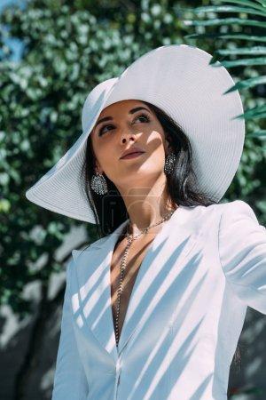 Photo pour Attrayant femme en costume blanc et chapeau posant et regardant loin à l'extérieur - image libre de droit