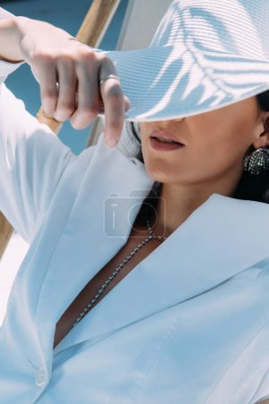 Photo for Adult woman in white suit and hat posing outside - Royalty Free Image