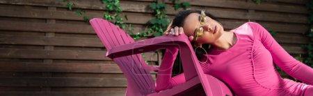 Photo pour Photo panoramique d'une femme séduisante en robe et lunettes de soleil posant à l'extérieur - image libre de droit