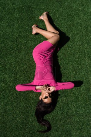 Photo for Top view of attractive woman in dress and sunglasses posing and lying on grass outside - Royalty Free Image